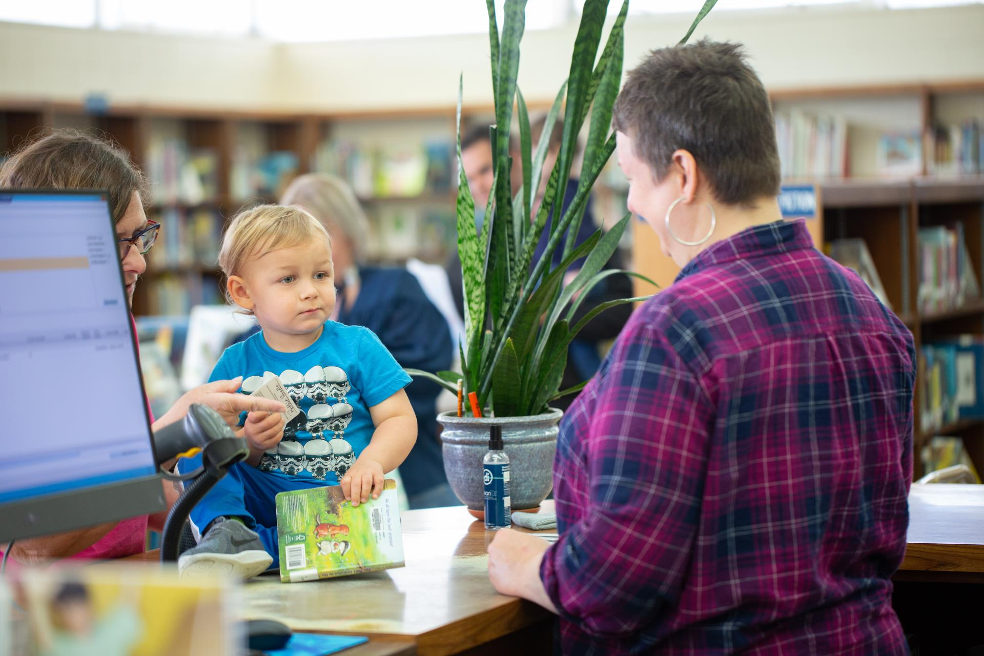 Image of Child checking out a book at library